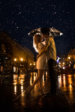Man and the girl kiss in the rain. Photo contains glare from lights. photo