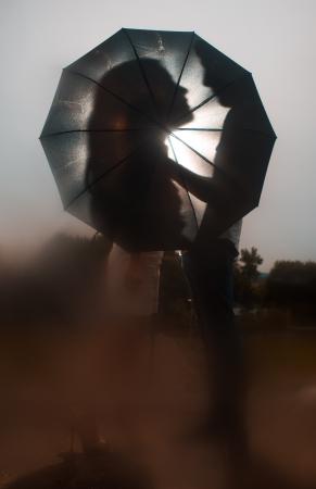 雨の傘の下でカップルをキスのシルエットの愛します。
