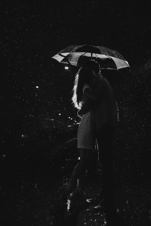 Love in the rain  Silhouette of kissing couple under umbrella photo