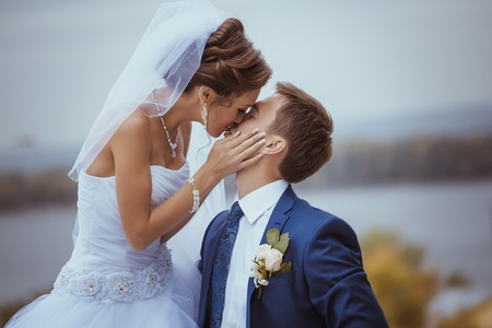 Young wedding couple kissing. Bright white colors. Stock Photo