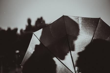 雨の中で愛のシルエット傘の下でカップルのキス