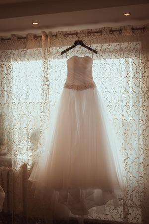 Wedding Dress Hanging in a Window Stock Photo