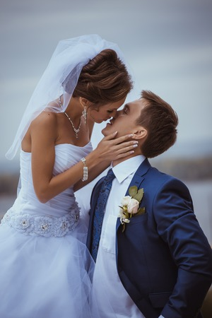 Young wedding couple kissing  Bright white colors
