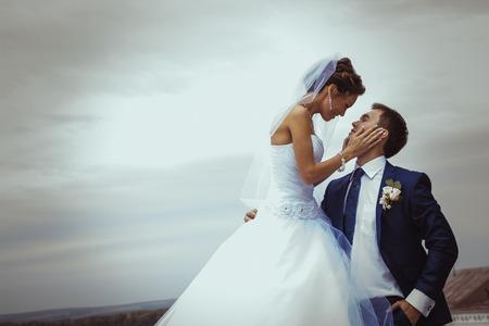 boda: Joven pareja de novios besándose brillantes colores blanco