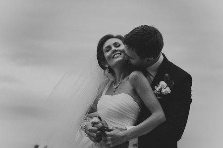 Young wedding couple kissing  Bright white colors  photo