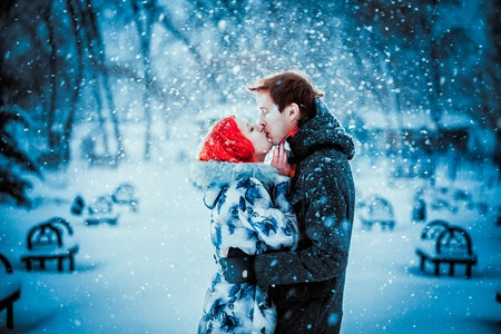 Happy Young Couple in Winter Park having fun.Family Outdoors. love kiss photo
