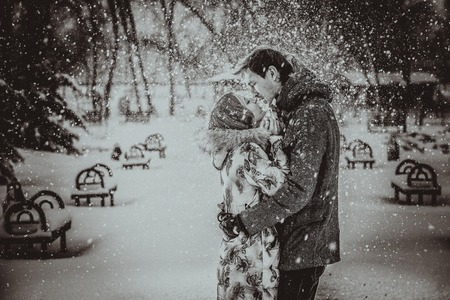 Young couple kissing on snow. Black and white. photo