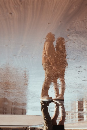 Reflection in puddle of woman and man embracing under umbrella during rain photo