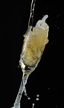 Glass of champagne with splash, isolated on black background photo