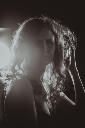 A black and white image of a beautiful young woman with flowing hair. Film noir style. Filtered photo