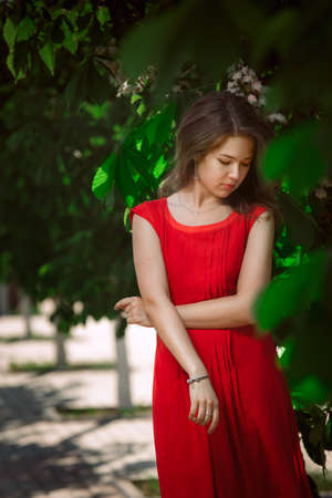 Portrait of a beautiful sexy fashion girl in a red dress on the nature of the park, with dark hair and a leather belt photo