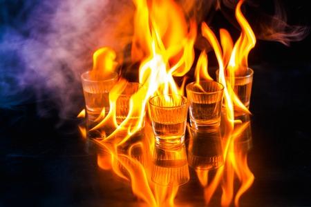 Glazen met brandende alcohol op zwarte achtergrond