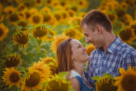 love couple standing outdoors in  sunflower field photo