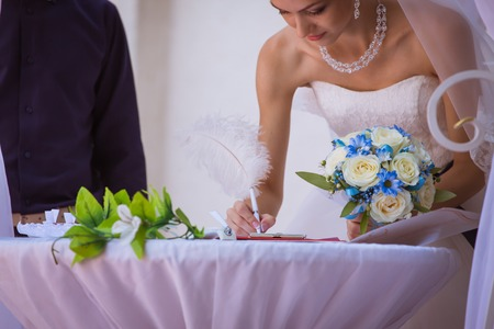 bride signing wedding certificate in park Stock Photo