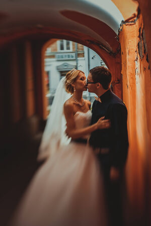 Closeup portrait of bride and groom kissing in ancient tunnel made of bricks