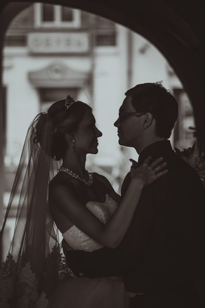 Closeup portrait of bride and groom kissing in ancient tunnel made of bricks photo