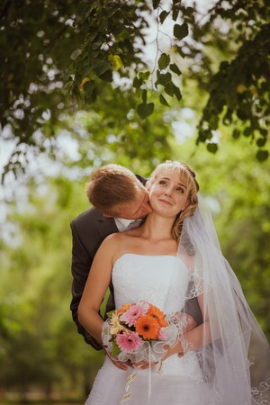 Bride and groom in a park kissing.couple newlyweds bride and groom at a wedding in nature green forest are kissing photo portrait.Wedding Couple Love