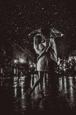 幸せなカップルが、雨の下でキス 写真素材