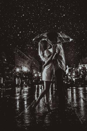 gelukkige paar kussen onder de regen