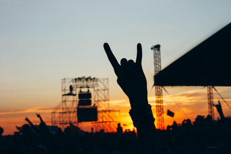 large rock: Rock concert, silhouettes of happy  people raising up hands