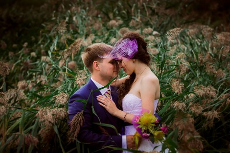 Young attractive bridal couple  holding hands outdoors next to tree by lake