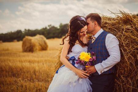 bride and groom near hay barn Stock Photo