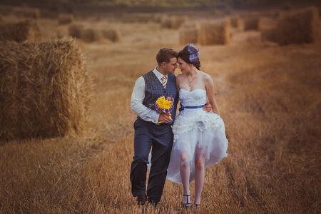 bride and groom near hay barn photo