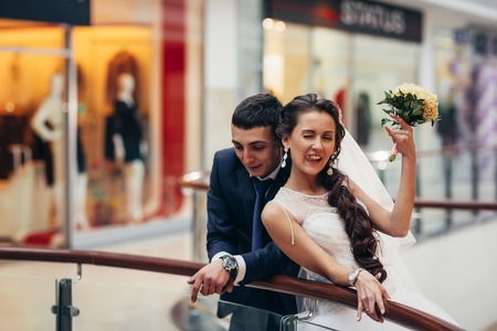 Happy bride and groom embracing  in the spacious hall of the shopping complex