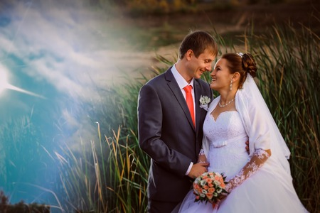 beautiful lovely bridal couple standing  near lake