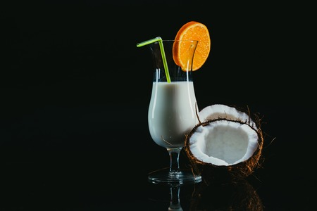 Pina Colada over black background, with coconut. Stock Photo