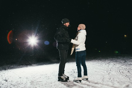 Couple ice skating outdoors on a pond on night photo