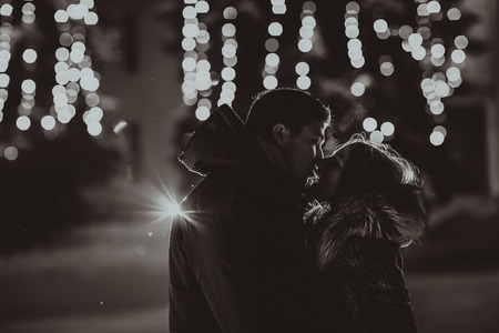 forbidden love: Silhouette of kissing couple with lights Stock Photo