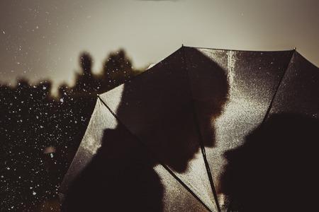 雨の中愛のシルエット傘の下でカップルのキス