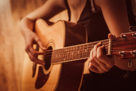 womans hands playing  acoustic guitar, close up