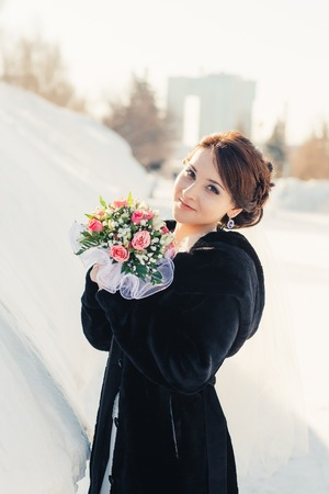 Beautiful bride with bouquet  posing outdoor in snow