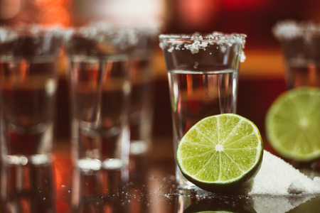 horizontal bar: two shots of tequila with lime and salt on a  wooden table bar on the background of bright lights of the bar Stock Photo