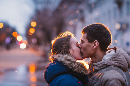 Portrait of young beautiful couple kissing in an autumn rainy day