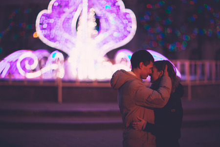 Portrait of young beautiful couple kissing in an autumn night