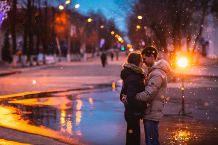 夜の街で雪の中で愛のカップル。穀物と光の点滅でフィルター