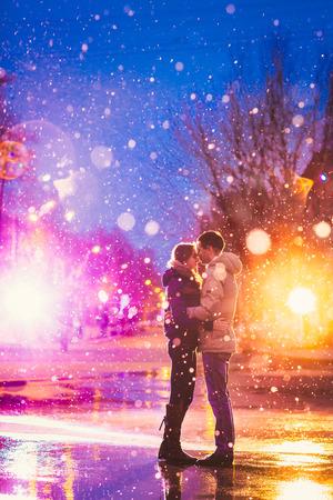 vestido de noche: En el amor pareja en la nieve en la calle de la ciudad de noche. Filtrado con grano y luz intermitente Foto de archivo