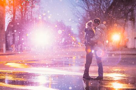В любви пара, поцелуи в снегу на ночь улицы города. Отфильтрованный с зерном и свет мигает Фото со стока