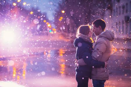 Verliefd paar in de sneeuw 's nachts stad straat. Gefilterd met graan en knipperend licht Stockfoto