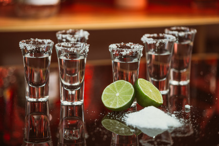 two shots of tequila with lime and salt on a  wooden table bar on the background of bright lights of the bar photo