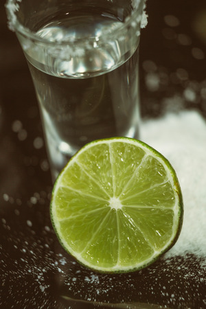 tequila with lime and salt on a wooden table bar photo
