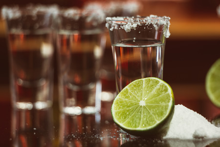 tequila with lime and salt on a  wooden table bar on the background photo