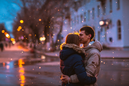 In love couple in the snow at night city street Stock Photo