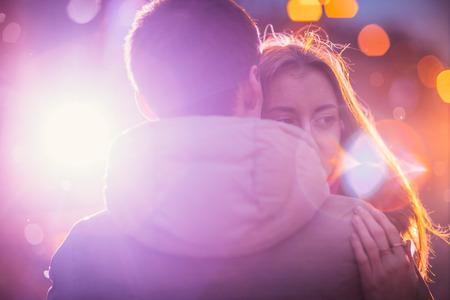 young couple kiss: En el amor pareja en la nieve en la calle de la ciudad de noche. Filtrado con grano y luz intermitente Foto de archivo