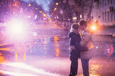 で愛カップルは、夜の街で雪の中でハグ。穀物と光の点滅でフィルター