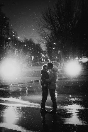 In de liefde paar kussen in de sneeuw 's nachts stad straat, zwart en wit