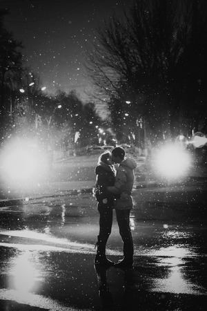 In love couple kissing in the snow at night city street, black and white
